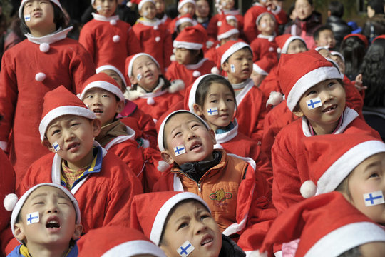 Primary school students dress up in Santa costumes as they look up at balloons in the sky in Nanjing