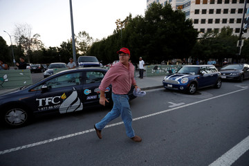 A supporter of Republican U.S. presidential candidate Donald Trump runs after being confronted by demonstrators after a campaign rally in San Jose