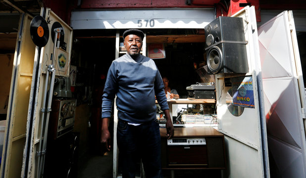 Vendor Rugami stands outside his second-hand vinyl record stall at the Kenyatta Market in Nairobi, Kenya