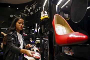 Carmen Dang, a design consultant, checks a display showcasing designs by Shoes of Prey located in a large department store in central Sydney, Australia