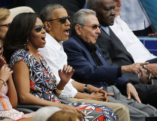 U.S. President Barack Obama and his wife react along with Cuban President Raul Castro to an exhibition baseball game in Havana