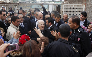 Beji Caid Essebsi (C), presidential candidate and leader of Tunisia's secular Nidaa Tounes party, reacts as he campaigns in Tunis
