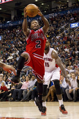 Bulls' Nate Robinson drives to the basket past Raptors' Amir Johnson in Toronto.