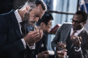 businessman smoking cigar with multicultural business team spending time behind
