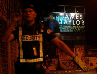 A billboard promoting a planned concert by American singer-songwriter James Taylor is seen in the background of a traffic enforcer directing traffic flow on a busy street in Mandaluyong, Metro Manila, Philippines