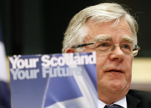 """Hudghton, SNP President, holds up a brochure reading """"Your Scotland Your Future"""" during a conference at the EP in Brussels"""