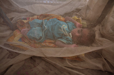 Benazir, a one-week-old girl, lies inside a mosquito net at a camp for flood victims in the Badin district of Pakistan