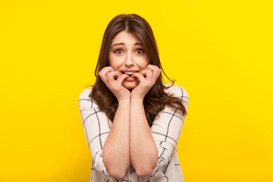 Scared girl posing on yellow