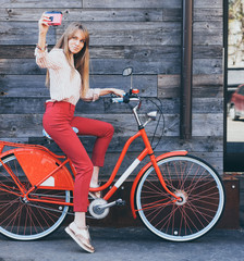 Pretty smiling young woman using taking self portrait on pink vintage camera with retro bicycle over old wood planks background