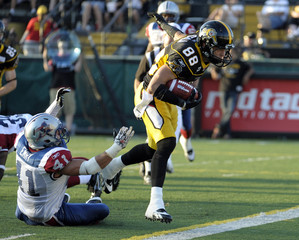 Tiger-Cats wide receiver Stala scores a touchdown against Alouettes defender Emry during their CFL football game in Hamilton