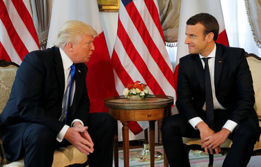 U.S. President Trump and French President Macron talk before a working lunch ahead of a NATO Summit in Brussels