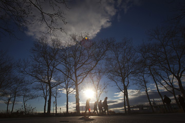 People walk in the late afternoon sun in Battery Park in the Manhattan borough of New York
