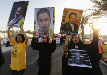Protesters holding placards with photos of human rights activists and doctors, demand their release as they march during an anti-government protest organised by Bahrain's main opposition party Al Wefaq in Budaiya