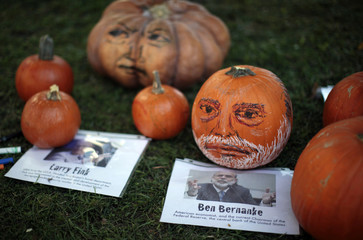 Pumpkins decorated with the faces of bankers are displayed at the Occupy LA protest camp in Los Angeles