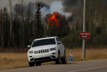 "A car is parked in front of a ""Wrong Way"" sign as flames from wildfires erupt near Fort McMurray"