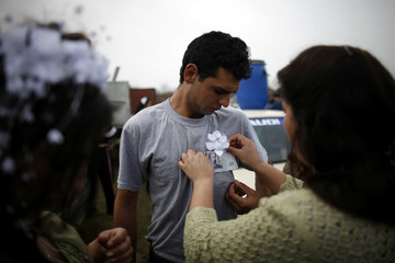 Bulgarian Roma woman from the close-knit Kalaidjii clan attaches a banknote to the shirt of a guest of a wedding ceremony during a bride fair in Mogila