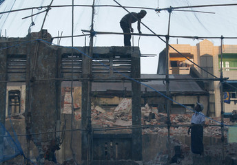 Labourers work at a demolition site of an old building in Yangon