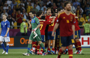 Italy's goalkeeper Buffon walks past Spain's players, as they celebrate their fourth goal during their Euro 2012 final soccer match at the Olympic stadium in Kiev