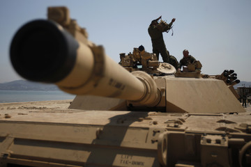 U.S. Marine soldiers take a rest on top of a M1A1 battle tank during the CJLOTS exercise on a seashore in Pohang