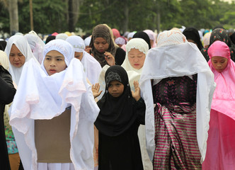 Filipino Muslims hold morning prayers in front of the Blue Mosque, in celebration of Eid-al-Adha, in Taguig city