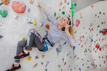 Woman climbing on climbing wall. The girl shows a victory gesture. Teenage rock climber.