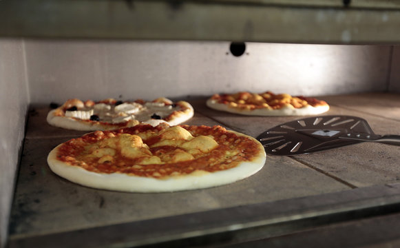Pizza pies are seen in an oven at the French pizzaiolo school in Cap D'Ail