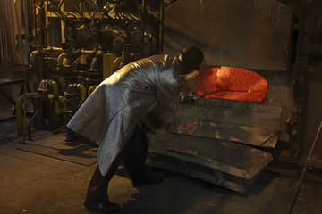 A worker cleans impurities from an aluminium furnace at Renault car engine factory in Cleon