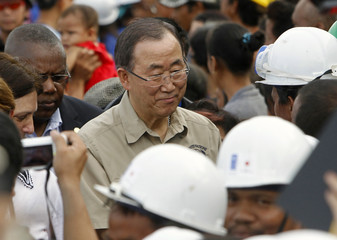 U.N. Secretary-General Ban is welcomed by a street sweeper after inspecting a devastated area of Fatima village at Tacloban city
