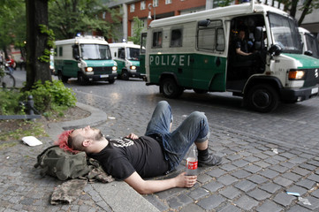 A left-wing protestor rests on a street during May Day demonstrations in Berlin's Kreuzberg district