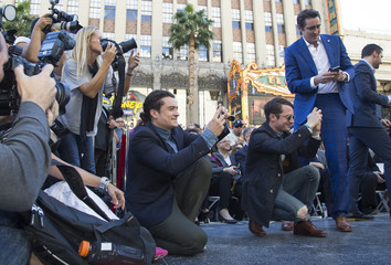 Actors Bloom, Wood and Pace use their mobile devices during the unveiling ceremony of the star for director Peter Jackson on the Walk of Fame in Hollywood