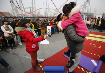A judge holds up a picture for a couple to mimic during a kissing contest held in celebration of Valentine's Day at the Happy Valley amusement park in Beijing