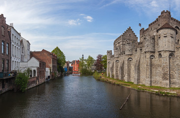 Panoramic view of medieval Gravensteen castle and canal with old picturesque traditional houses in historic part of Ghent, Belgium