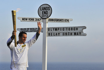 British Olympic sailor Ainslie carries the Olympic torch on the first leg of its Britain Northern Ireland and Ireland tour at Lands End in Cornwall, south west England