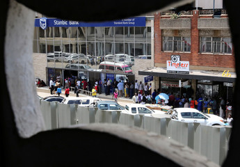 Locals queue to withdraw cash from a bank in Harare