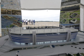 The model of a new Kaliningrad stadium, which is expected to host the 2018 World Cup matches, is on display, with the construction site seen in the background in the Baltic Sea port of Kaliningrad, Russia.
