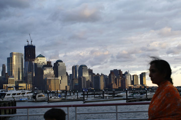 With the skyline of New York in the background, people walk during sunset at the Jersey City Waterfront Walkway along Hudson river in New Jersey