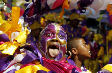 Brightly coloured revellers sing and dance through the streets of Cape Town, during the Cape Minstrel Festival