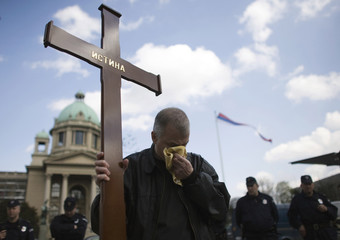 A man pretends to cry as he holds a wooden cross during a protest against the state's decision to apologize to victims of the 1995 Srebrenica massacre, in front of Serbian Parliament building in Belgrade