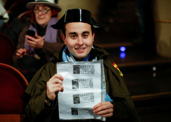 """A man dressed as a civil guard displays photocopies of lottery tickets as he attends the draw of Spain's Christmas Lottery """"El Gordo"""" (The Fat One) in Madrid"""