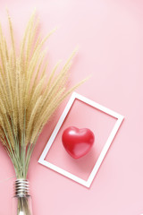 dry Flower and red heart in White picture frame on pink background ,copy space