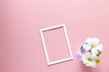 Flower in the cup and White picture frame on pink background ,copy space