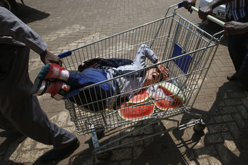 Security forces use a shopping cart to transport the injured after unidentified gunmen went on a shooting spree at the Westgate shopping mall in Nairobi, Kenya