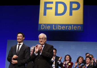 German Economy Minister Roesler and leader of the FDP smiles after he delivered his speech while party fellow Bruederle applauds during a two-day party convention in Berlin