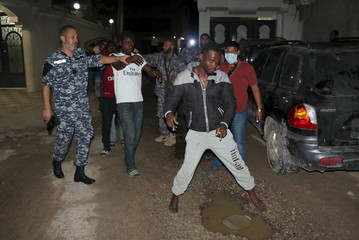 Officers of a Libyan anti-illegal immigrants unit conduct an early morning raid on migrants at hideout in Tripoli