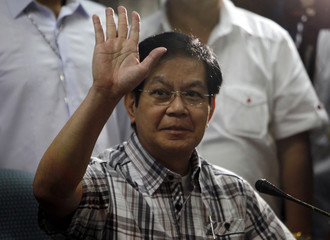 Senator Panfilo Lacson waves to reporters before the start of a news conference at the Senate headquarters in Pasay city, metro Manila