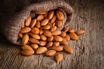 Almond. Nuts on textured wooden background. Organic food.