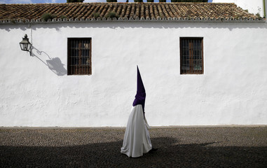 """A penitent walks before the procession of """"La Sangre"""" brotherhood during Holy Week in Cordoba"""