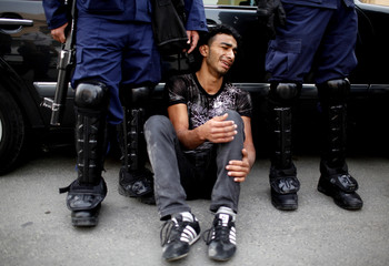 An anti-government protester, injured during a fall while running away from the police, holds his leg while being detained by riot policemen during clashes in the village of Sanabis, west of Manama