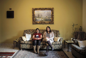 Hala Tanmus and her daughter Maya pose for a picture in the living room of their home in the West Bank city of Ramallah