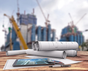 blueprints and tablet on office table in the construction site